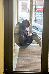 A homeless person asleep in a doorway