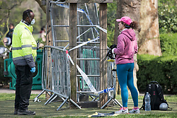 © Licensed to London News Pictures. 28/03/2020. London, UK. A woman wanting to use exercise equipment talks to a member of security wearing a medical face mask, stood next to exercise equipment that has been cordoned off, at Paddington Recreation Ground in London, during a lockdown over the spread of COVID-19. Prime Minister Boris Johnson has announced that people should only leave their homes for essential work, groceries, medical necessity and exercise. Photo credit: Ben Cawthra/LNP