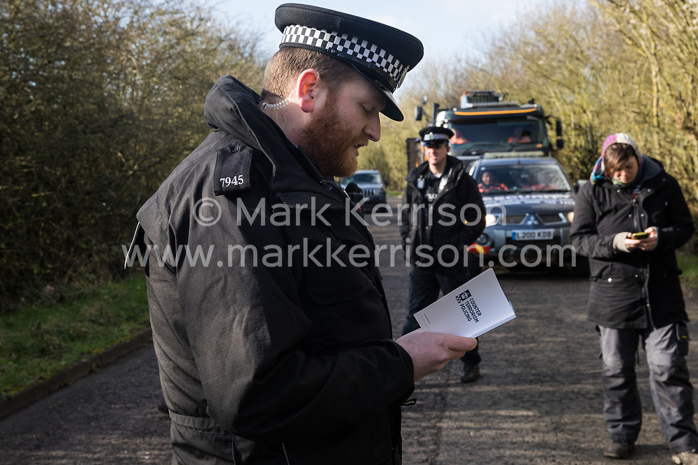 Denham, UK. 11 February, 2020. A Thames Valley Police officer reads from a book entitled 'Counter Terrorism Policing' as he issues a warning to an environmental activist from Extinction Rebellion who had been 'slow walking' in front of a truck delivering a JCB forklift truck to a HS2 site. The activist was subsequently arrested.