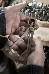 Senior male goldsmith measuring a metal ring, Bavaria, Germany