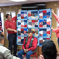 Manuel Troncos, 89, sits in front of his quilt that is presented by John Matajcich, and Mayor Jackie Mckinney at the Veterans Helping Veterans building in Gallup Friday.