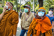 26 DECEMBER 2013 - BANGKOK, THAILAND:  Buddhist monks and a spectator watch for riot police during an anti-government riot in Bangkok. Thousands of anti-government protestors flooded into the area around the Thai Japan Stadium to try to prevent the drawing of ballot list numbers by the Election Commission, which determines the order in which candidates appear on the ballot of the Feb. 2 election. They were unable to break into the stadium and ballot list draw went as scheduled. The protestors then started throwing rocks and small explosives at police who responded with tear gas and rubber bullets. At least 20 people were hospitalized in the melee and one policeman was reportedly shot by anti-government protestors.     PHOTO BY JACK KURTZ