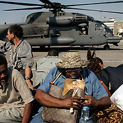 NEW ORLEANS, LA - September 4, 2005:  Evacuees from New Orleans were being flown to the city's airport via helicopter and unloaded on the tarmac. Unloaded on the tarmac in a scene similar to that of a war zone evacuation, they were then hustled from the helicopter onto waiting cargo carts ( normally used to move luggage) and rushed amid a throng of volunteers and into the airport where they received medical attention. Shortly after entering the airport, evacuees were screened and divided nto groups of 50 and told to go to a certain boarding gate. Evacuees only find out the destination of the flight, and their new temporary home, after boarding the flight. (Photo by Todd Bigelow/Aurora)..Julia Chaney, clutching her Dr. Martin Luther King fan, which she had held onto since the storm struck on Monday, and family are taken from helicopter.......Members of the Chaney family, Kenneth (large man with straw hat), Anthony (other man with shorts), Elaine (younger woman), and Julia (woman with MLK prayer fan and hat--she's Ken's and Anthony's mother). Joseph (yellow shirt,using cane to walk) and Velma (red shorts and white ball cap). Joseph and Velma are Elaine's parents...... (Last name TK--check with reporter ken lee)..