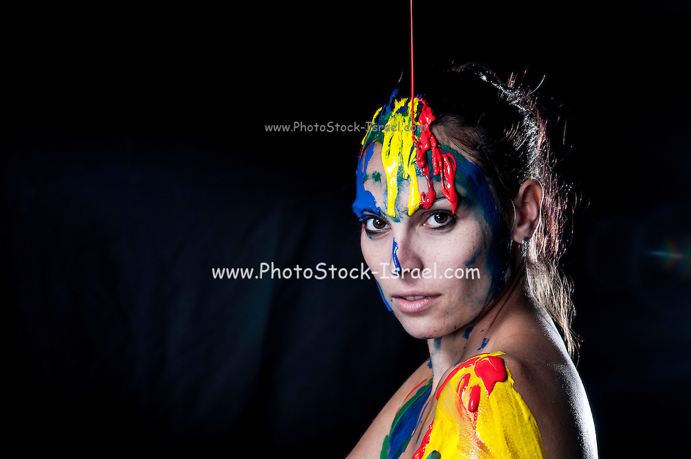Young Woman pours paint over her face and head