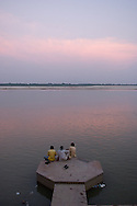 People relax at the end of the day on the edge of the holy Ganges River in Varanasi, India.