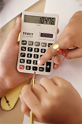 Close up of primary school child using calculator in practical maths lesson,