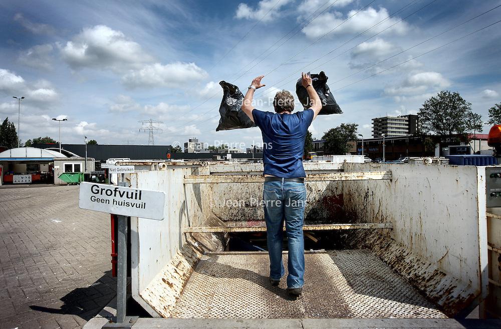 Nederland, Schiedam , 3 juli 2012..NV Irado in Schiedam is een veelzijdig bedrijf. Irado zamelt huishoudelijk afval in voor 4 gemeenten, beheert de openbare ruimte voor Schiedam en levert een scala aan diensten voor lokale overheden en het midden- en kleinbedrijf..Al de werkzaamheden van Irado zijn erop gericht onze klant zoveel mogelijk te ontzorgen. Dat uit zich in integraal, oplossingsgericht en proactief te werken..De 300 medewerkers van Irado zetten zich dagelijks in voor een schone, verzorgde en opgeruimde leefomgeving en voelen zich betrokken en verantwoordelijk hiervoor. Hun kennis, ervaring en passie geven ze graag door aan anderen, zoals de deelnemers aan het ?Social Return? project van de gemeente Schiedam..Op de foto: bewoner van Schiedam gooit afval in de afvalcontainer van het milieupark Irado ..Foto:Jean-Pierre Jans
