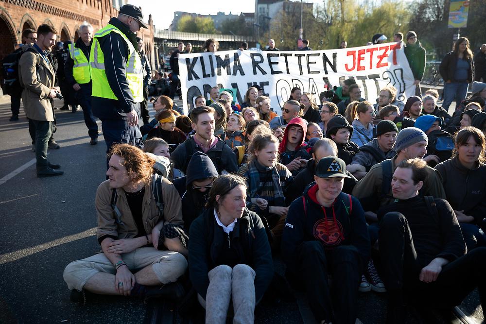 """Aktivisten von Extinction Rebellion (XR)  blockieren im Rahmen der der internationalen Rebellionswoche unter dem Motto """"Aktion Spreebrücken - Friedlich, zivil & ungehorsam!"""" die Oberbaumbrücke in Berlin. Weltweit protestieren Menschen in 40 Ländern im Namen von Extinction Rebellion gegen die Klimapolitik und fordern sofortige Klimaschutzmaßnahmen. Demonstranten mit Banner: Klima retten jetzt.<br /> <br /> [© Christian Mang - Veroeffentlichung nur gg. Honorar (zzgl. MwSt.), Urhebervermerk und Beleg. Nur für redaktionelle Nutzung - Publication only with licence fee payment, copyright notice and voucher copy. For editorial use only - No model release. No property release. Kontakt: mail@christianmang.com.]"""