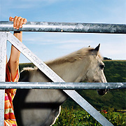 Farmer's daughter Rebecca Hawkins (hanging off a metal gate) and her horse 'Merry Legs', Warren Farm, Exmoor, Somerset, UK