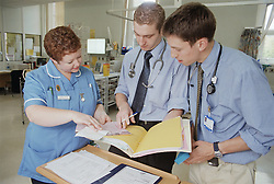 Two doctors and senior staff nurse discussing patient's notes,