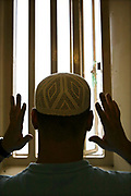A Muslim prisoner praying in his cell. HMP Wandsworth, London, United Kingdom