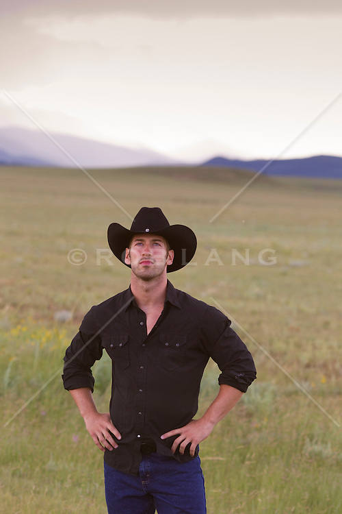 handsome cowboy standing in a field in New Mexico