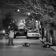 A police officer looking over the bodies of two men who were executed and left hooded and bound on a city street in Cuidad Juarez, Mexico.<br /> (Credit Image: © Louie Palu/ZUMA Press)