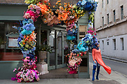 A visitor to London poses in front of the flowers that decorate the exterior of a cafe on Brewer Street in the heart of Soho in the West End, on 18th February 2020, in London, England.