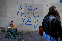 © Licensed to London News Pictures. 18/09/2014. Glasgow, UK. People go past a 'Vote Yes' graffiti on their way to polling stations in Glasgow to vote on the Scottish independence referendum on Thursday, 18 September 2014. Photo credit : Tolga Akmen/LNP