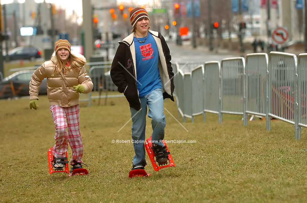 Siblings, Lydon, 13, left, and Austyn Horvath, 11, of Windsor Canada attempt to run in snowshoes at the Winter Blast Festival held in downtown Detroit, MI Friday, Feb. 3, 2006. Warm weather foiled plans to make snow for the festival which was to include many winter activities such as dog sledding and snowshoeing. (Robert Caplin For The New York Times)..