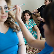 (L-R) Manhaz Rafat age 30 seen having her makeup done as her sister Nargis Merzai age 28 has her hair done by their sister Sheela Dost age 15 the day of Nargis's son Farhan's first birthday. For a follow up story on the Dost family. A family of Afghans who escaped the war in Afghanistan in the 1990's, escaped to Pakistan and immigrated to Canada in 2004 as refugees and now live in Winnipeg, Manitoba. (Credit Image: © Louie Palu/ZUMA Press)