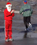POCATELLO, N.Y. - A man wearing a Santa Claus costume cheers for runners near the finish line of the  Jingle Jog road race.