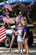Mount Pleasant, United States of America. 04 July, 2020. Children wave flags during an Independence Day parade  despite a dramatic rise in COVID-19, coronavirus cases in Charleston County July 4, 2020 in Mount Pleasant, South Carolina. South Carolina is currently number three nationwide in number of infected per population.  Credit: Richard Ellis/Alamy Live News