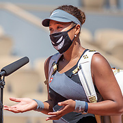 PARIS, FRANCE May 30. Naomi Osaka of Japan conducts an on court interview while wearing a mask after her victory against Patricia Maria Tig of Romania in the first round of the Women's Singles competition on Court Philippe-Chatrier at the 2021 French Open Tennis Tournament at Roland Garros on May 30th 2021 in Paris, France. (Photo by Tim Clayton/Corbis via Getty Images)