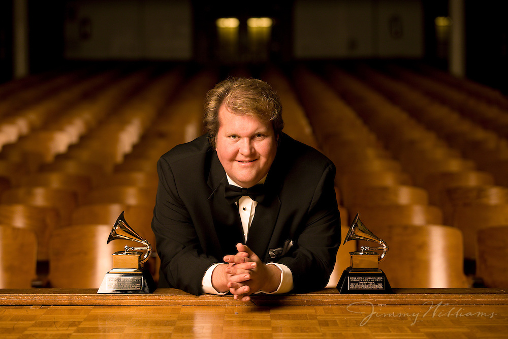 An opera singer leans forward with his awards on display inside an old theater.