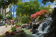 Flowers and waterfall fountain at Kuhio Beach Park, Waikiki Beach, Honolulu, Oahu, Hawaii