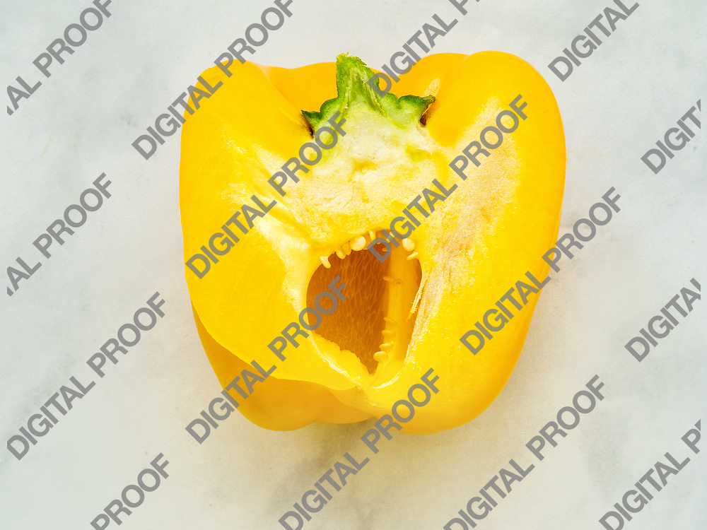 Yellow bell pepper sliced by the half with seeds isolated in kitchen counter viewed from above- macro and detail concept