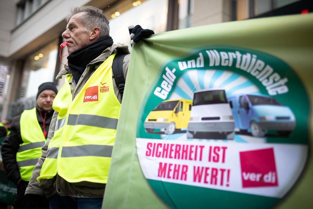 Über hundert Fahrer von Geldtransportern protestieren während des Warnstreiks vor der 6. Verhandlungsrunde zwischen der Bundesvereinigung Deutscher Geld- und Wertdienste (BDGW) und ver.di in der Friedrichstrasse in Berlin. Die Gewerkschaft fordert eine Erhöhung des Stundenlohns um 1,50 € bei einer zweijährigen Laufzeit. Demonstrant mit Banner: Sicherheit ist mehr wert!<br /> <br /> [© Christian Mang - Veroeffentlichung nur gg. Honorar (zzgl. MwSt.), Urhebervermerk und Beleg. Nur für redaktionelle Nutzung - Publication only with licence fee payment, copyright notice and voucher copy. For editorial use only - No model release. No property release. Kontakt: mail@christianmang.com.]