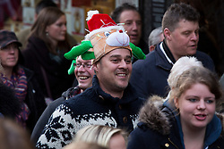 "© Licensed to London News Pictures. 7/12/2013. Lincoln, UK. Lincoln City Centre was packed with Christmas shoppers this weekend. Pictured, probably the one day in the year when you can get away with wearing a silly hat on the High Street. Thousands of shoppers filled the City Centre and stewards were called in to direct people up the narrow ""Steep Hill"" towards the upper area of Lincoln near the Cathedral. Photo credit : Dave Warren/LNP"