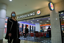 © Licensed to London News Pictures. 17/10/2021. London, UK. A woman walks past Burger King in north London. There are fears that fast food chains could start running out of fry bags and other packaging, due to a shortage of HGV lorry drivers. Photo credit: Dinendra Haria/LNP
