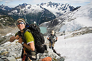 Climbers Brian Polagye, left, and Jim Prager rope up below Eldorado Peak, North Cascades National Park, Washington. Forbidden Peak and Moraine Lake are visible in the background.