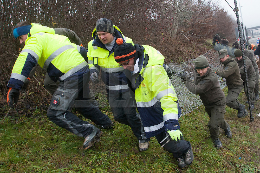 Licensed to London News Pictures. 08/12/2015. Spielfeld, Austria. Austrian soldiers and workers are building a wire fence to stop the migrants at the border crossing between Austria and Slovenia. Photo: Marko Vanovsek/LNP