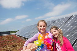 Two girls sitting next to photovoltaic panel