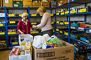 Two female volunteers prepare an emergency food package at Wadebridge foodbank, North Cornwall, England, United Kingdom. The food bank is part of the Trussell Trust charity which provides assistance to individuals and families in crisis and living below the poverty line.