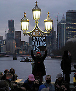 """A woman stands above the crowd of protestors holding a sign that states """"stop killing us"""" aimed at the police following the recent killing of Sarah Everard. London. March 15th 2021."""