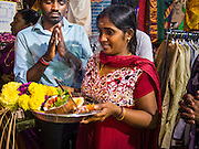 04 OCTOBER 2014 - GEORGE TOWN, PENANG, MALAYSIA: People pray as a procession honoring Durga is drawn through the streets of George Town during the Navratri procession. Navratri is a festival dedicated to the worship of the Hindu deity Durga, the most popular incarnation of Devi and one of the main forms of the Goddess Shakti in the Hindu pantheon. The word Navaratri means 'nine nights' in Sanskrit, nava meaning nine and ratri meaning nights. During these nine nights and ten days, nine forms of Shakti/Devi are worshiped.   PHOTO BY JACK KURTZ