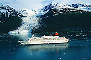 Alaska. Prince William Sound. A cruise ship carries passengers through icy College Fjord, Chugach Mts beyond.