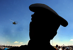KABUL,AFGHANISTAN - SEPT. 9: An Afghan police officer watches an ISAF helicopter patrol  Kabul Sports Stadium September 9, 2002  during a ceremony to comemerate the anniversary of the death of Ahmad Shah Massoud in Kabul, Afghanistan. (Photo by Ami Vitale/Getty Images)