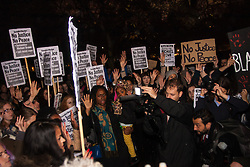 """London, November 26th 2014. A vigil for teenager Mike Brown who was shot dead by a policeman in Ferguson, Missouri this year, takes place outside the US embassy in London. Anti-racism and human rights campaigners called the 'emergency' protest following a court verdict that clears Police Officer Darren Wilson of murder. PICTURED: Part of the several hundred-strong crowd puts their hands up in a """"Don't shoot!"""" gesture against trigger-happy policing."""