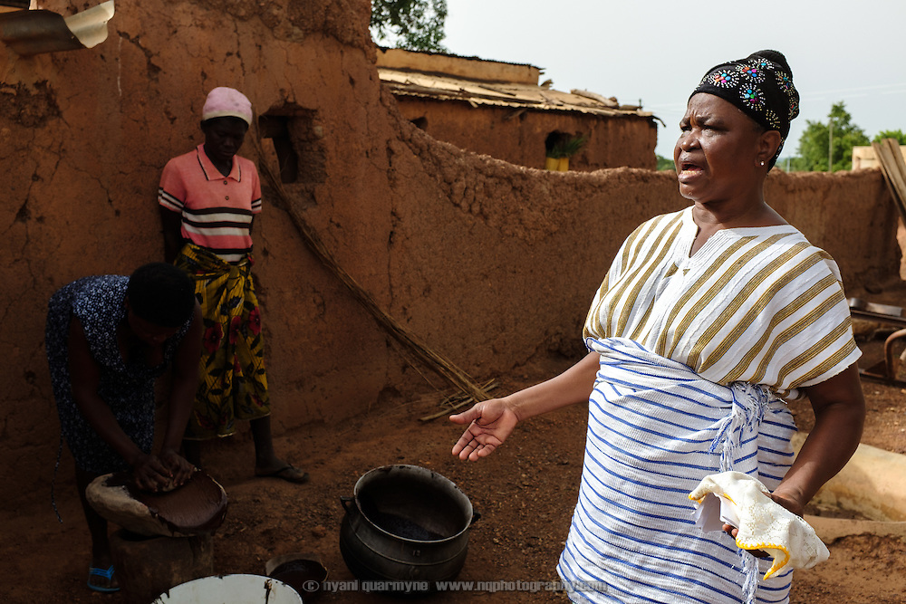 """Pognaa Dogkudome Tegzuylle I with women making shea butter in her home village of Lyssah in the Upper West Region of Ghana. Though incredibly labour-intensive, shea butter production provides an important income stream for many women in the Upper West, and is one major focus the Pognaa's development efforts in her community. The term """"pognaa"""" is the feminine equivalent of """"naa"""", or chief. A pognaa is responsible, in particular, for the wellbeing of women and children in her area of authority. While the title translates as """"woman chief"""", in practice her authority is  subject to a male chief. The role of the pognamine (plural of pognaa) is being revived after having been suppressed during the colonial era, and they are increasingly seen as a force for development."""