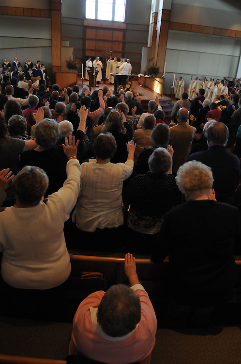 Parishioners outstretch their hands during the dedication mass Sunday, Nov. 22.