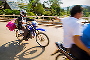 12 MARCH 2013 - ALONG HIGHWAY 13, LAOS:  Motorcycles on Highway 13 use the bridge over the Nam Kor River in Oudomaxy. The paving of Highway 13 from Vientiane to near the Chinese border has changed the way of life in rural Laos. Villagers near Luang Prabang used to have to take unreliable boats that took three hours round trip to get from the homes to the tourist center of Luang Prabang, now they take a 40 minute round trip bus ride. North of Luang Prabang, paving the highway has been an opportunity for China to use Laos as a transshipping point. Chinese merchandise now goes through Laos to Thailand where it's put on Thai trains and taken to the deep water port east of Bangkok. The Chinese have also expanded their economic empire into Laos. Chinese hotels and businesses are common in northern Laos and in some cities, like Oudomxay, are now up to 40% percent. As the roads are paved, more people move away from their traditional homes in the mountains of Laos and crowd the side of the road living off tourists' and truck drivers.    PHOTO BY JACK KURTZ