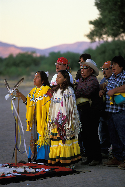 An Apache girl and her helper, both dressed in buckskin dresses, dance at the girl's Sunrise Dance, a first menstruation rite, on the San Carlos Indian Reservation, Arizona, USA. The girl holds a cane that symbolises longevity. Behind her the medicine man and drummers sing and beat their drums. The Sunrise Dance is supposed to prepare the girl for adulthood and to give her a long and healthy life without material wants.The ceremony is also an enactment of the Apache creation myth and during the rites the girl 'becomes' Changing Woman, a mythical female figure, and comes into possession of her healing powers.