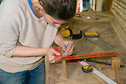 Female carpenter measures and marks a length of wood in preparation of a dovetail joint