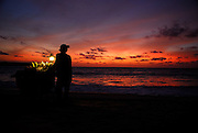 Sweet-corn vendor with cart on beach, silhouetted against setting sun. Jimbaran Bay, Bali, Indonesia. Jimbaran Bay was the location of the second Bali terrorist bombing on October 2, 2005.