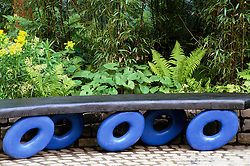 A wooden bench seat with blue painted 'wheels'. A Garden for Learning, Chelsea Flower Show 200. Design: Cleve West