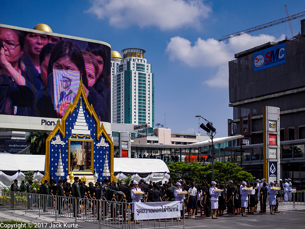 26 OCTOBER 2017 - BANGKOK, THAILAND:  People leave sandalwood flower offerings while the funeral is broadcast of national television during the funeral ceremony for Bhumibol Adulyadej, the Late King of Thailand. The king died on 13 October 2016 and was cremated 26 October 2017, after a mourning period of just over one year. The revered monarch was the longest reigning king in Thai history and is credited with guiding Thailand through the turbulent latter half of the 20th century.   PHOTO BY JACK KURTZ