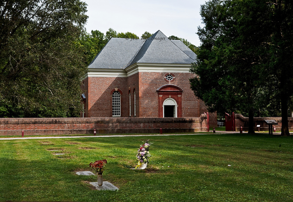 """Perfect American Georgian brick church, funded by Robert """"King"""" Carter in 1735.  Central plan, carved walnut pews and pulpit.  Carfully preserved and devotedly maintained by a private organization.  Seen from the southeast across the graveyard, two honored with fresh flower bouquets."""
