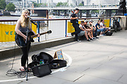 Young busker (Charlotte Campbell) performing her music, both singing and playing guitar on the South Bank. The South Bank is a significant arts and entertainment district, and home to an endless list of activities for Londoners, visitors and tourists alike.