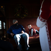"""STRASBURG, PA:  Blake <br /> Messick, 2, greets Dave Saunders, 46, in his 7th year as Santa, during  a holiday steam train attraction """"Santa Express, on the oldest continually operated railroad in the country, in Strasburg, PA on December 13, 2020. The pandemic has forced difficult decisions about maintaining the holiday tradition of visits to Santa Claus versus safety concerns.  Plexiglass dividers, face shields, and physical distancing are among the precautions for those locations that have proceeded with Santa photo opportunities.  CREDIT:  Mark Makela for The New York Times"""